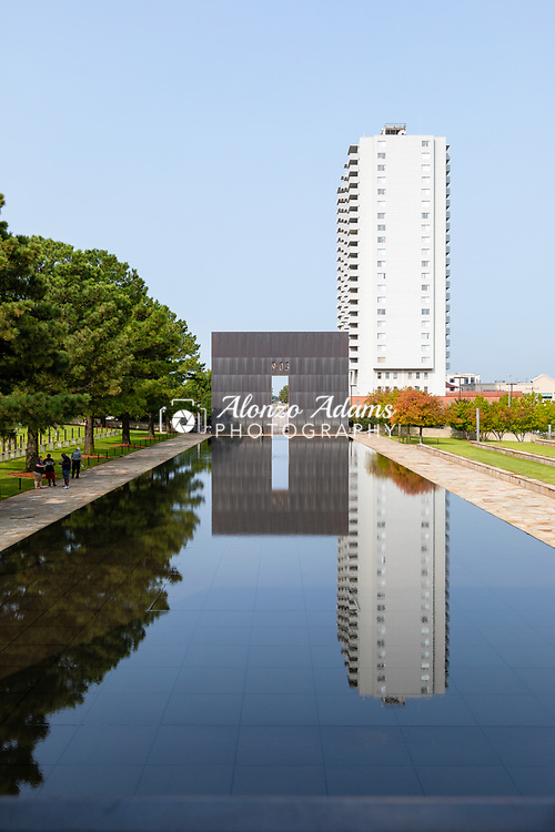 People stand along side the Oklahoma City National Memorial and Museum reflecting pool on Sunday, September 13, 2020. The memorial honors the victims, survivors, rescuers, and all who were affected by the Oklahoma City bombing on April 19, 1995. Photo copyright © 2020 Alonzo J. Adams.