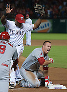 The Angels' Mike Trout celebrates his leadoff triple in the top of the ninth inning next to Rangers' third baseman Adrian Beltre during the Halos' 2-1 victory Friday night at Globe Life Park in Arlington, Texas.