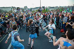 London, UK. 20th April 2019. Climate change activists dance as the XR Samba Band performs on Waterloo bridge, which has been blocked by Extinction Rebellion for six days. During that time, they have created a Garden bridge used for International Rebellion activities to demand urgent action to combat climate change by the British government.