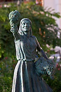 Statue of a girl holding a bunch of grapes and a basket by R Cuello. Sitges, Catalonia, Spain