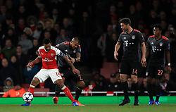 Arsenal's Theo Walcott (left) and Bayern Munich's Arturo Vidal battle for the ball