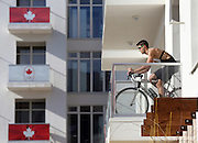 A member of the Canadian team takes advantage of warm weather to work out on his balcony in Olympic Village at the Winter Olympics in Sochi, Russia, Thursday, Feb. 6, 2014. (Brian Cassella/Chicago Tribune/MCT)