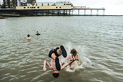 © Licensed to London News Pictures. 29/07/2018. Aberystwyth, UK. Teenagers have fun jumping off the jetty, despite it being a grey, wet and overcast Sunday at the seaside in Aberystwyth on the west Wales coast. The long heatwave finally breaks down with thunderstorms and torrential rain over much of the country. photo credit:  Keith Morris/LNP