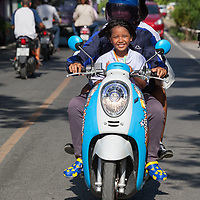 A man and his daughter driving a motorcycle in Ayutthaya.