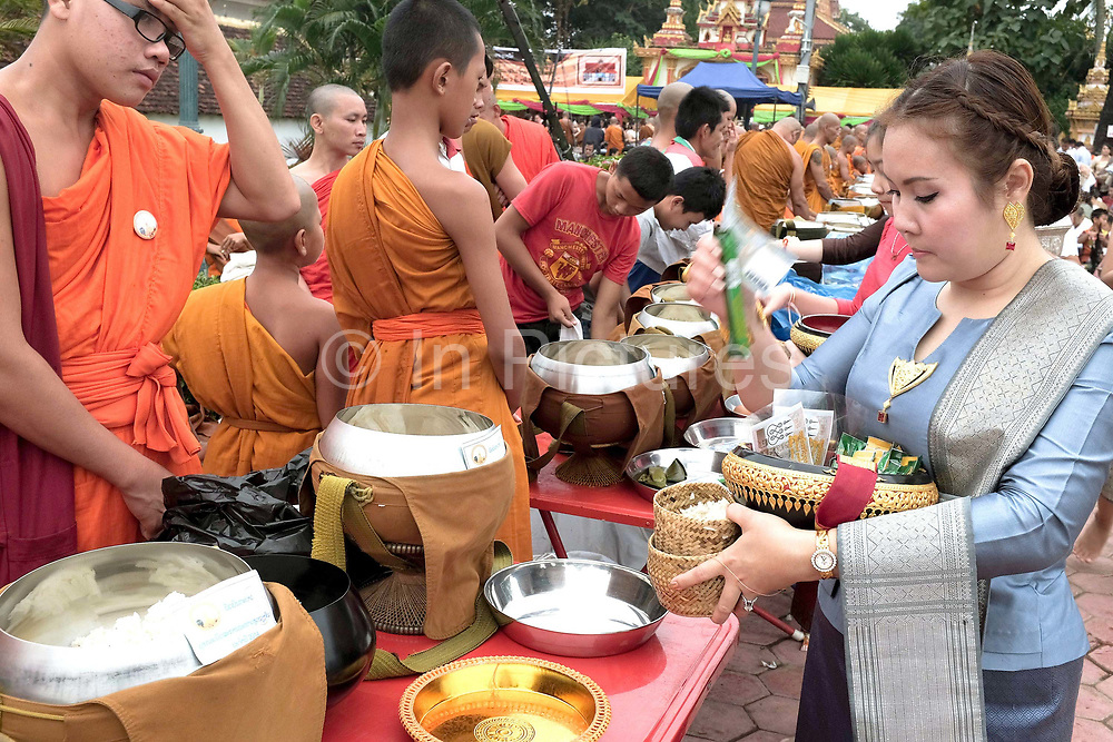 """Alms giving (tak bat) at That Luang festival, Vientiane, Lao PDR. Pha That Luang is the national symbol and most important religious monument of Laos. Vientiane's most important Theravada Buddhist festival, """"Boun That Luang"""", is held here for three days during the full moon of the twelfth lunar month (November). Monks and laypeople from all over Laos congregate to celebrate the occasion with three days of religious ceremony followed by a week of festivities, day and night. The procession of laypeople begins at Wat Si Muang in the city centre and proceeds to Pha That Luang to make offerings to the monks in order to accumulate merit for rebirth into a better life. The religious part concludes as laypeople, carrying incense and candles as offerings, circumambulate Pha That Luang three times in honor of Buddha."""