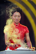"""A woman cooks a fish as an electric current passes through her body, part of the game show called """"Who's the Hero"""" at Hunan TV. The station's Producers say their formula for success is simple: creating zany and off-beat entertainment programs."""