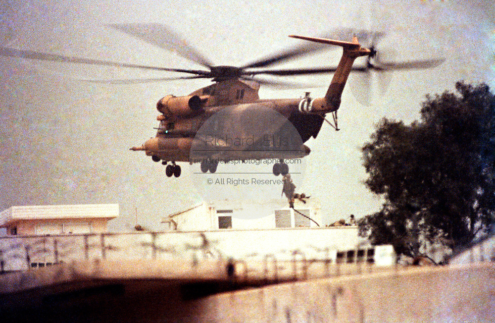 US Marine Corps commandos rappel from a helicopter as they recapture the U.S. Embassy with skies darkened by oil fires February 28, 1991 in Kuwait City, Kuwait.  The Marines took control of the embassy after defeating occupying Iraqi forces.