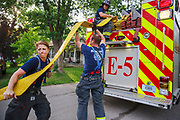 Members of the Bloomington Fire Department pick up hoses after putting out a fire in the 2400 block of S. Broadview Drive, Friday, June 7, 2019 in Bloomington, Ind. When firefighters arrived the house was smoking and flames were shooting out of the back of a house, and a second alarm was called. However, the firefighters put out the flames before the fire could spread more. The fire began before 6:45 p.m.
