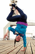 Young female breakdancing doing a handstand with one hand