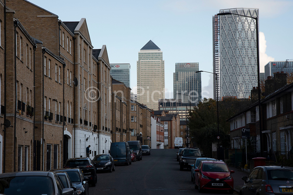View looking along a residential street in Bermondsey towards Canary Wharf and the Docklands financial district on 5th November 2019 in London, England, United Kingdom. Canary Wharf is the secondary central business district of London and is situated on the Isle of Dogs. It is one of the main financial centres in the world, containing many of the tallest buildings, including the second-tallest in the UK, One Canada Square.