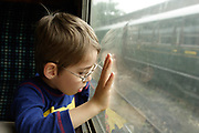 A young boy looks out of the window of a carriage on the Bluebell Steam Railway. E Sussex. UK May 29th 2008