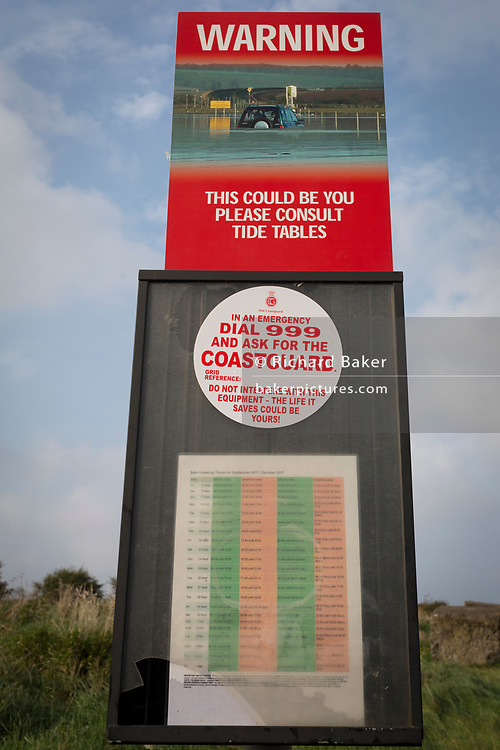 One of the warning signs alerting motorists of tidal dangers on the causeway between the tidal Lindisfarne island and the Northumbrian mainland, on 27th September 2017, on Lindisfarne Island, Northumberland, England. Despite tide timetables posted all over the area, drivers often mis-time their crossings, their vehicles ending up submerged in salt water. The small Lindisfarne population of just over 160 is swelled by the influx of over 650,000 visitors from all over the world every year. A tidal Island: Lindisfarne is a tidal island in that access is by a paved causeway which is covered by the North Sea twice in every 24 hour period. The Holy Island of Lindisfarne, also known simply as Holy Island, is an island off the northeast coast of England. Holy Island has a recorded history from the 6th century AD; it was an important centre of Celtic and Anglo-saxon Christianity. After the Viking invasions and the Norman conquest of England, a priory was reestablished.
