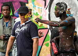 © Licensed to London News Pictures. 25/08/2019. London, UK. A member of the public has paint squirted in his face as he passes by revellers enjoying J'ouvert, a paint fight that officially marks the start of the Notting Hill carnival. The two day event is the second largest street festival in the world after the Rio Carnival in Brazil, attracting over 1 million people to the streets of West London. Photo credit: Ben Cawthra/LNP