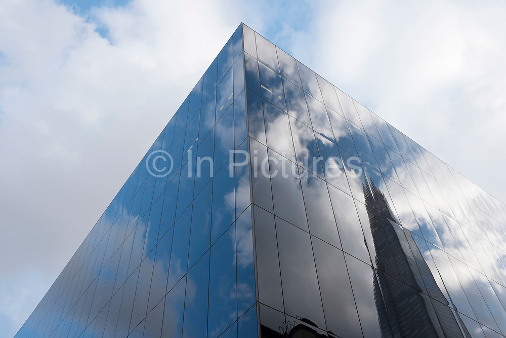 Glass building reflecting the clouds and The Shard in a blue sky. Modern architecture interacting with nature at More London, UK. More London is an office development containing many professional services and financial services firms.