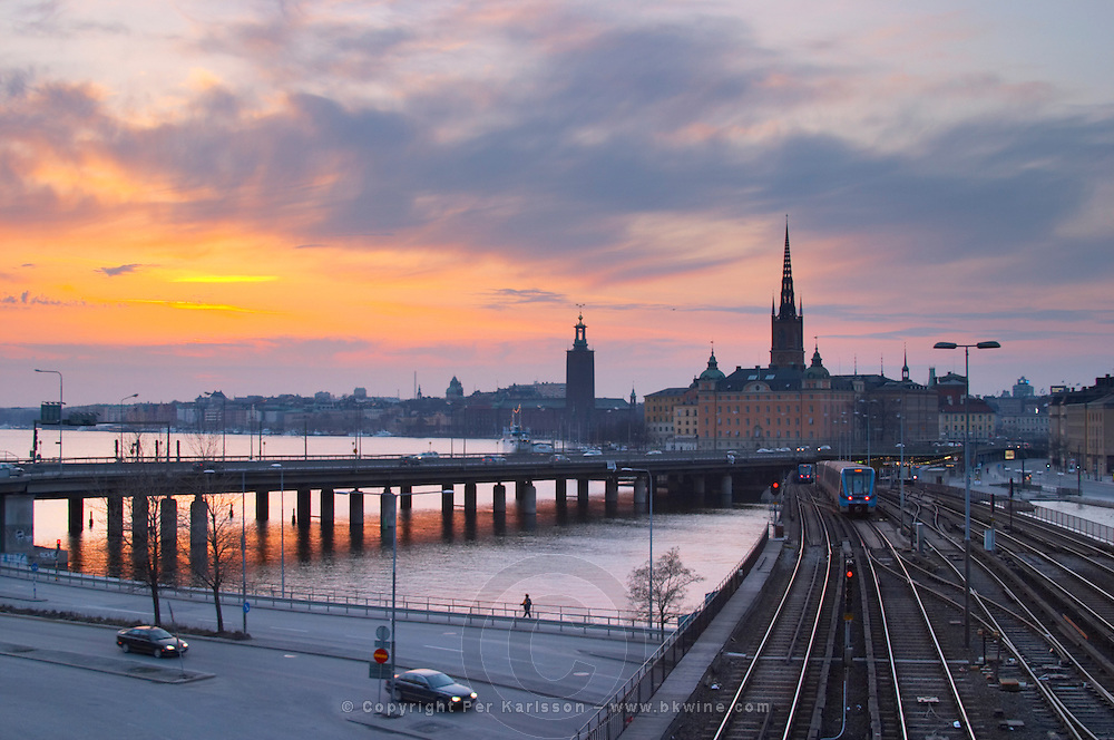 The bridge at Slussen with Riddarholmen and the Stadshuset in the background at sunset with colourful orange sky. The Stockholm subway. Stockholm. Sweden, Europe.