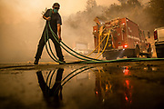 A man pulls out a garden hose as he helps Fire Fighters with Cal Fire protect the St. Helena Water Treatment Plant from the Glass Fire in Napa Valley, CA on September 27, 2020. The fire began in the early morning hours and quickly grew to more than 1,500 acres.