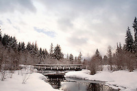The bridge reflects in the River of Golden Dreams, on a snowy winter day in Whistler, BC CANADA