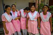 A group of schoolgirls laughing and posing for a photograph outside a classroom at their school, Sursuna High School, Sursana, Kolkata, India