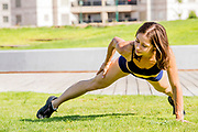 Young female bodybuilder exercises outdoors in a park