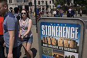 Advertising board selling trips to Stonehenge. Tourists heading to the Tower of London are enticed to other famour tourist destinations in the UK.