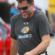 Driver Tony Stewart laughs at a joke in the pit area during the first practice session of the 56th Annual NASCAR Coke Zero400 race at Daytona International Speedway on Thursday, July 3, 2014 in Daytona Beach, Florida.  (AP Photo/Alex Menendez)