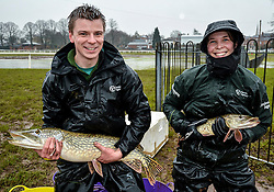 © London News Pictures. 28/02/2014. Worcester, UK.   Members of the Environment Agency holding two large pike fish rescued after being trapped on Worcester racecourse when flood waters subsided. Fish, including roach, perch, bream and pike, some weighing over 10lbs, were caught using a large hand net. Photo credit: LNP