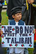 """A young boy holds a placard that reads """"We do not trust the Taliban"""" during a protest organised by the Afghan women along with their family members outside the Houses of Parliament in central London on Wednesday, Aug 18, 2021. VX Photo/ Vudi Xhymshiti)"""