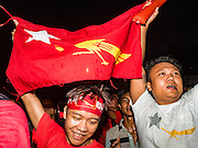 08 NOVEMBER 2015 - YANGON, MYANMAR:  A National League for Democracy supporter with a NLD flag cheers as another vote for the NLD was announced during the vote count Sunday. The vote count was shown live on television. The citizens of Myanmar went to the polls Sunday to vote in the most democratic elections since 1990. The National League for Democracy, (NLD) the party of Aung San Suu Kyi is widely expected to get the most votes in the election, but it is not certain if they will get enough votes to secure an outright victory. The polls opened at 6AM. In Yangon, some voters started lining up at 4AM and lines were reported to long in many polling stations in Myanmar's largest city.   PHOTO BY JACK KURTZ