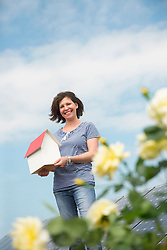 Woman holding model house roses clean energy
