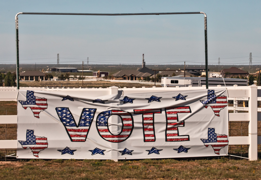 Drilling rig behind a home in Midland Texas near a voting sign before the midterm elections.