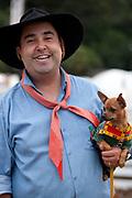 Portrait of male Gaucho cowboy holding small dog. Gaucho cowboy Rodeo, Flores de Cunha, Rio Grande do Sul.