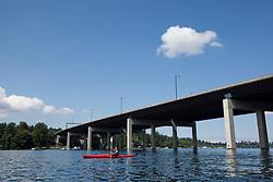 North America, United States, Washington, Bellevue, teenage boy kayaking under I90 highway bridge to Mercer Island.  MR