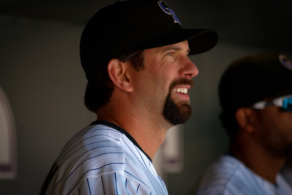 TODD HELTON watches game action from the dugout at Coors Field.
