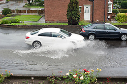 16:46 Ecclesfield Sheffield UK.The rain has deposited so much water it has flooded all the way across Minster Road..5 July 2012.Image © Paul David Drabble