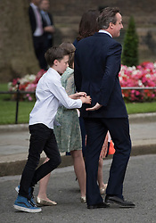 © Licensed to London News Pictures. 13/07/2016. London, UK. Prime Minister David Cameron's son Arthur reaches out to hold his father's hand as they leave Downing Street for the last time.  Photo credit: Peter Macdiarmid/LNP