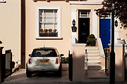 Front door of a house with a Mini car parked in the drive in Notting Hill, London. Showing various eras of architecture. Londoner's homes.