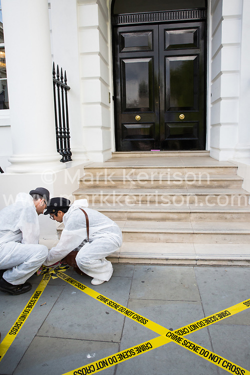 London, UK. 2 July, 2019. Crime scene stickers posted by climate change activists from Extinction Rebellion Art and Culture before a silent procession visiting the offices of five major oil companies - ENI, CNPC, Saudi Aramco, Repsol and BP - to declare them a crime scene.