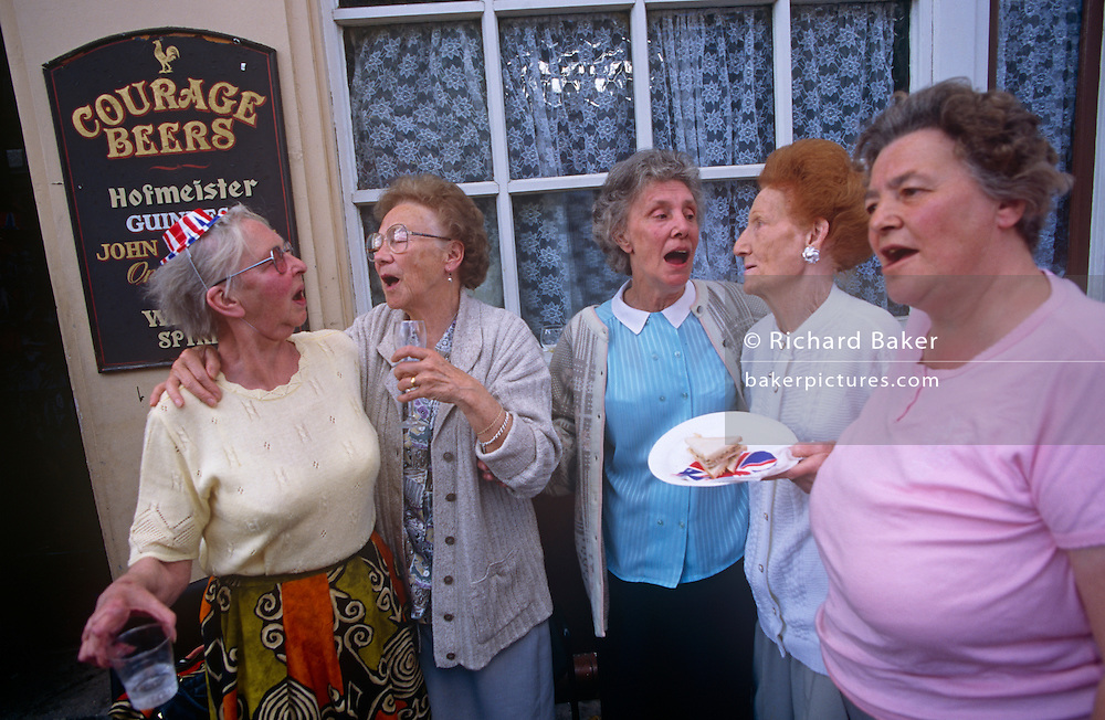 Elderly Londoners sing wartime songs during 1995 VE Day 50th anniversary street party in London's East End. The women open their mouths and belt out the tunes that they learned during wartime, helping them keep up morale during dark times during WW2. In the week near the anniversary date of May 8, 1945, when the World War II Allies formally accepted the unconditional surrender of the armed forces of Germany and peace was announced to tumultuous crowds across European cities, the British still go out of their way to honour those sacrificed and the realisation that peace was once again achieved. Street parties now – as they did in 1945 – played a large part in the country's patriotic well-being.