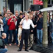 AMSTERDAM, 10-07-2013. Hans Klok heeft vanmorgen voor Carré en boven de Amstel een riskante en spectaculaire truc uitgevoerd. Vastgesnoerd in een dwangbuis wordt hij 15 meter omhoog en op zijn kop getakeld boven het water van de Amstel. Het touw wordt in brand gestoken waarna Hans 60 seconden de tijd heeft om zich te bevrijden voordat de vlijmscherpe Klauwen des Doods dichtklappen. Als hij zich heeft bevrijd zal Hans in het water van de Amstel springen. De Hongaarse Houdini nam voor dezelfde stunt een kwartier de tijd waar Hans dit in slechts 60 seconden probeert te doen.