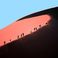 "Africa, Namibia, Sossusvlei. Visitors hike the crest of ""Big Mama"" sand dune in Sossusvlei."