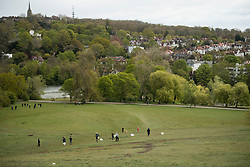 © Licensed to London News Pictures. 04/05/2021. London, UK. A group of children play with makeshift kites in strong winds on Hampstead Heath in North London. High winds and heavy rain are affecting parts of the UK today. Photo credit: Ben Cawthra/LNP