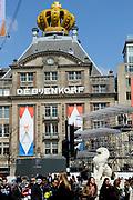 In Amsterdam worden de laatste voorbereidingen getroffen voor de troonswisseling op 30 april. <br /> <br /> The final preparations for the crowning on April 30, in Amsterdam.<br /> <br /> Op de foto / On the photo:  De Bijenkorf op de Dam draagt twee gouden kronen <br /> <br /> De Bijenkorf on Dam has two gold crowns