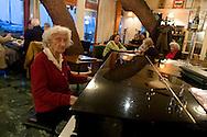 Trieste, una Signora anziana suona il pianoforte al Principe di Metternich,storico locale sulla baia di Grignano.