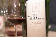 Cuvee l'Infidele. Domaine Mas Cal Demoura, in Jonquieres village. Terrasses de Larzac. Languedoc. France. Europe. Bottle. Wine glass.