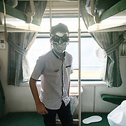 Kid wearing a scary masque. Overnight train from the holy city of Mashhad to the desert city of Yazd, known for its  zoroastrian community and wind towers.<br /> <br /> Travelling over 4000km by train across Iran. An opportunity to enjoy Persian hospitality, discover Iran's ancient cities and its varied landscapes, from deserts to mountains.