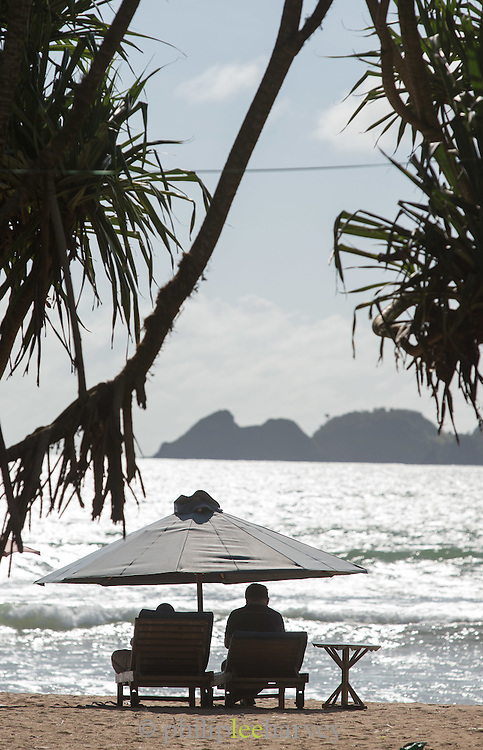 Couple sit on sun loungers beneath umbrella on beach, Red Island, Banyuwangi Regency, East Java, Indonesia, Southeast Asia