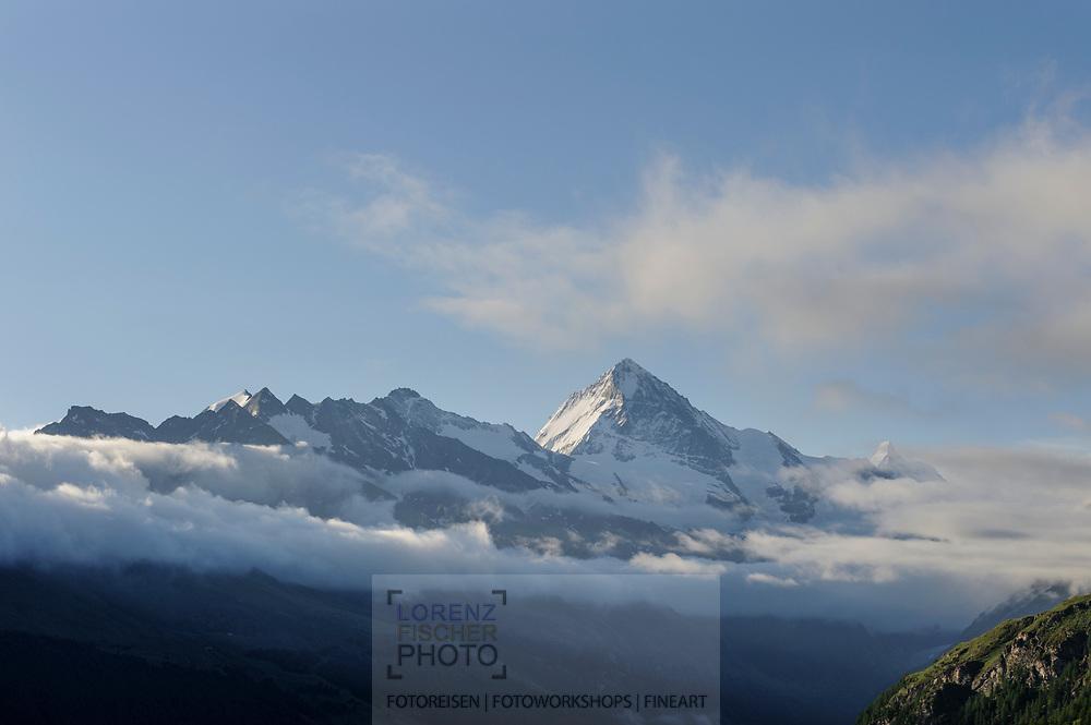 Wolkenverhangene Berge im Val d'Hérens oberhalb Evolène bei der Alp Chemeuille mit der Dent Blanche im Hintergrund.