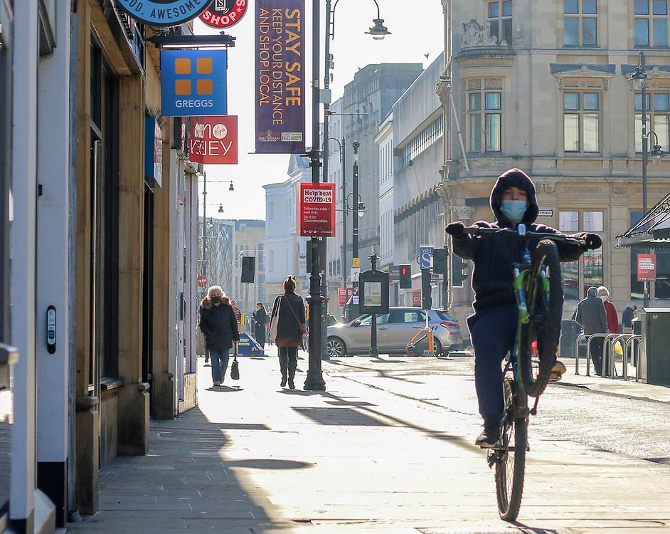 27th February, Cheltenham, England. A cyclist performs a wheelie through Cheltenham Town centre during the third national lockdown.
