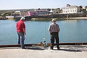 Two men look over harbour, Kilronan, Inishmore, Aran Islands, Irelanc