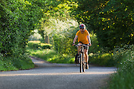 Cyclist framed by overhanging green-leafed trees on a country lane near Bradbourne, Peak District National Park, Derbyshire